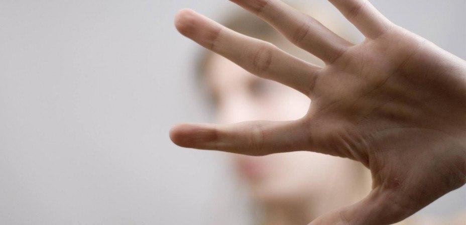 Foto: Junge Frau schützt ihr Gesicht mit der Hand vor der Kamera