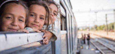 Foto: Drei Mädchen auf der Flucht strahlen aus einem Zugfenster