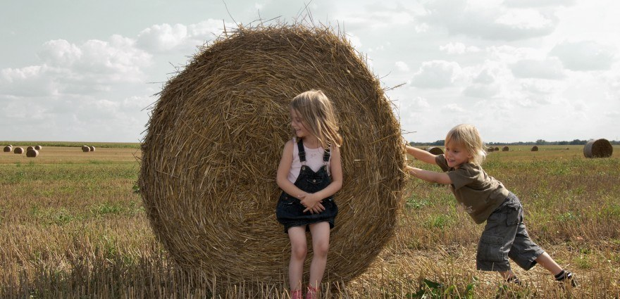 Foto: Zwei Kinder spielen mit Heuballen