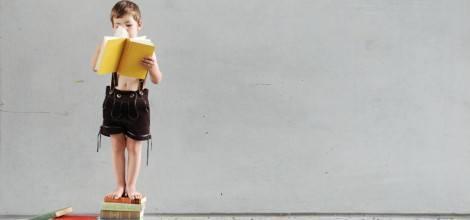 Foto: Kleiner Bub in der Lederhosen liest auf einem Bücherstapel