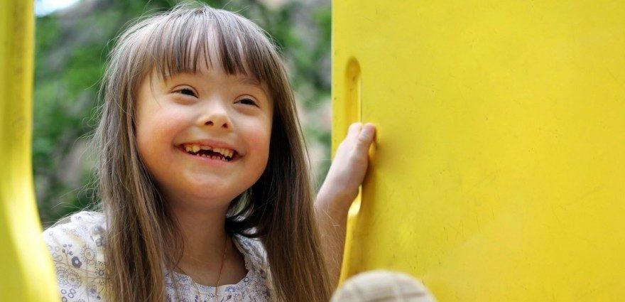 Foto: Kleines Mädchen mit Downsyndrom strahlt in die Kamera