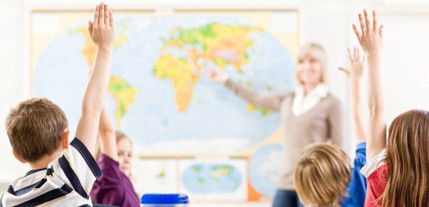 Foto: Mehrere Kinder melden sich im Klassenzimmer
