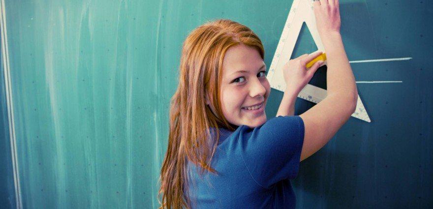 Foto: Teenagerin steht in der Schule an der Tafel