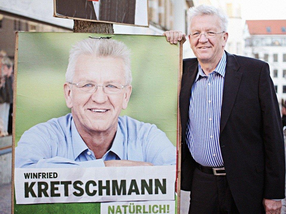 Foto: Winfried Kretschmann steht neben seinem Plakat