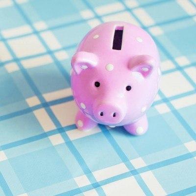 Foto: Sparschwein auf karierter Tischdecke