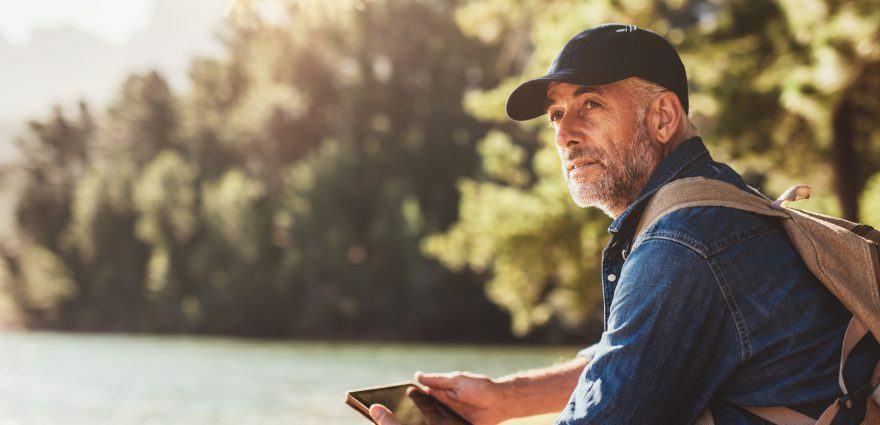 Älterer Mann mit Tablet in der Natur