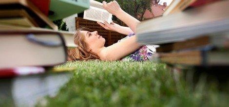 Foto: Junge Frau liegt auf der Wiese und liest ein Buch