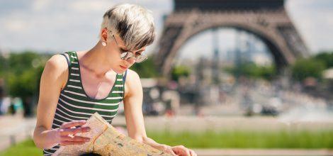 Foto: Junge Frau studiert eine Karte vor dem Eifelturm