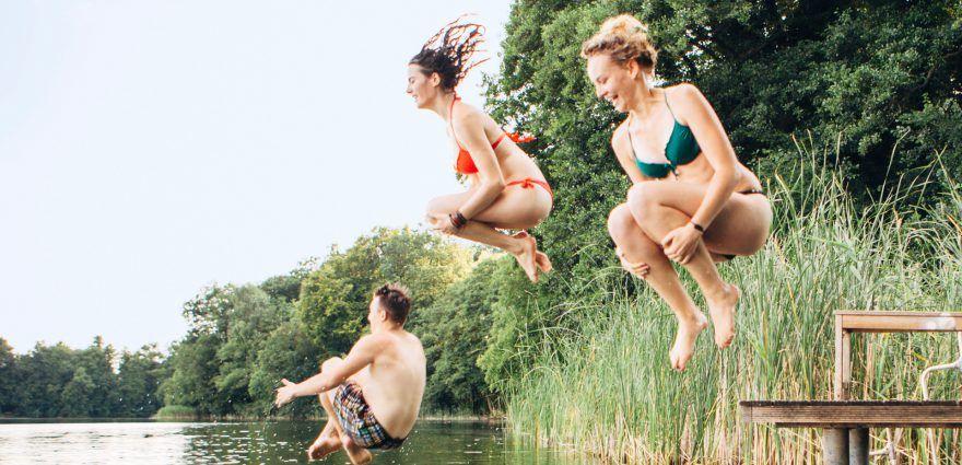 Foto: Drei junge Menschen springen in einen See