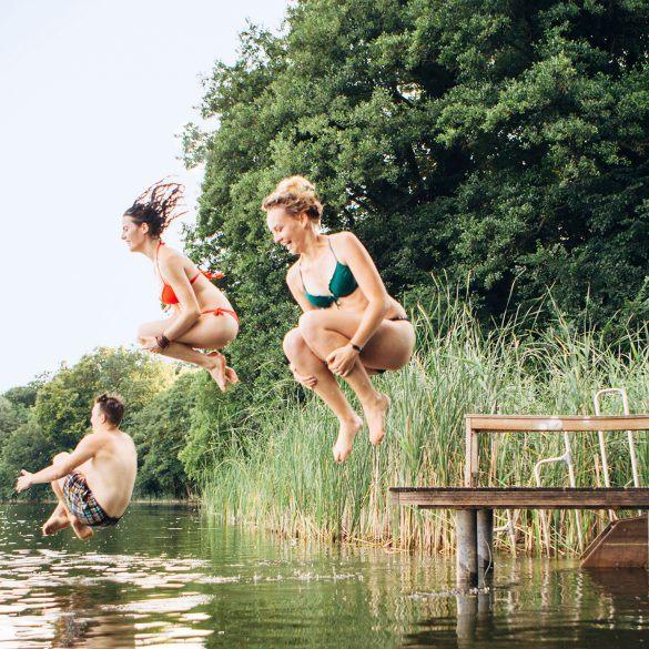 Foto: Drei junge Menschen springen vom Steg in einen See