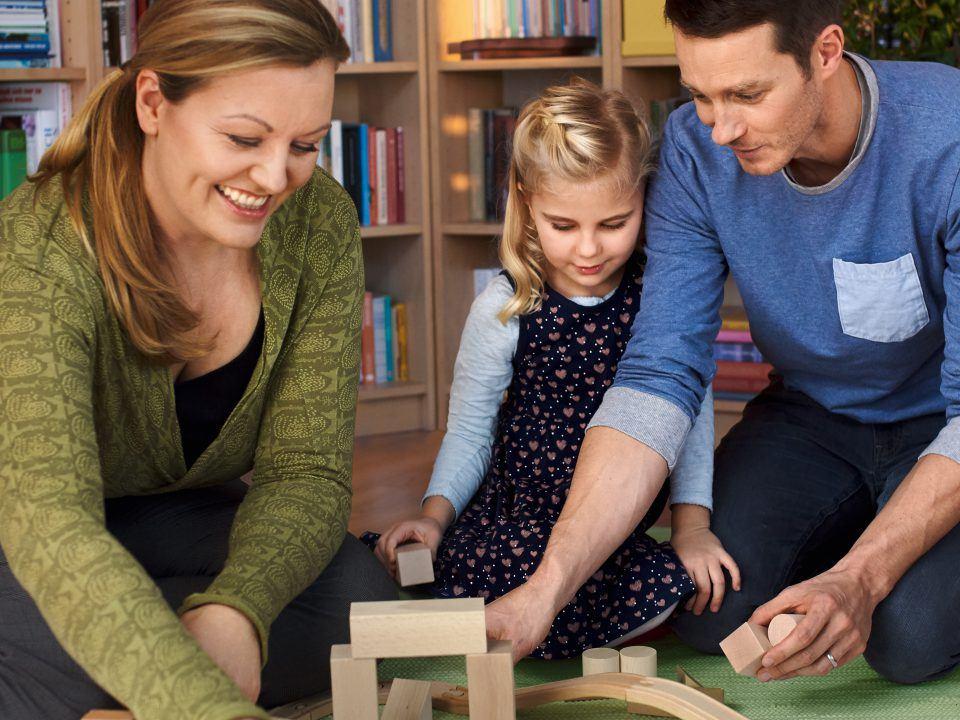 Foto: Eine Familie spielt mit Bauklötzen