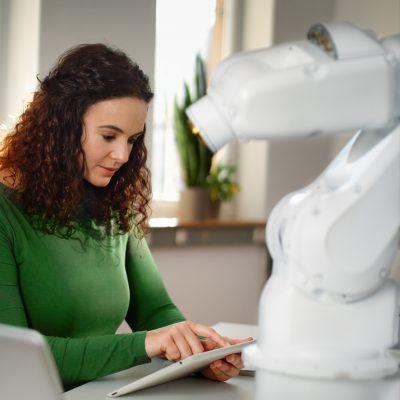 Foto: Junge Frau bedient einen Roboterarm mit dem Tablet