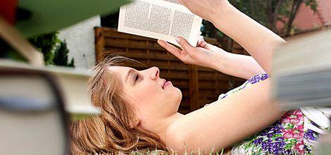 Foto: Junge Frau liegt auf der Wiese und liest