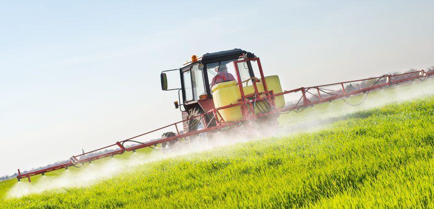 Foto: Ein Traktor versprüht Spritzmittel auf dem Feld