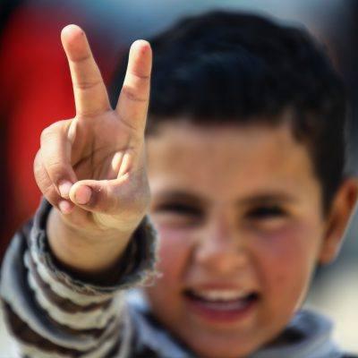 Foto: Flüchtlingsjunge zeigt Peace-Zeichen