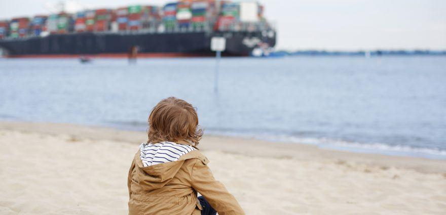 Foto: Kleiner Junge beobachtet Containerschiff vom Strand aus