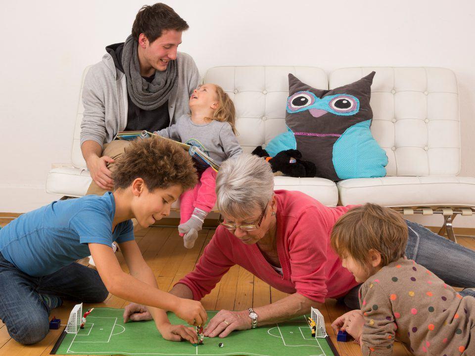 Foto: Oma spielt mit ihren Enkeln Tippkick