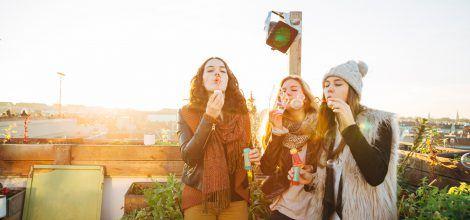 Foto: Junge Frauen spielen auf einer Dachterrasse mit Seifenblasen