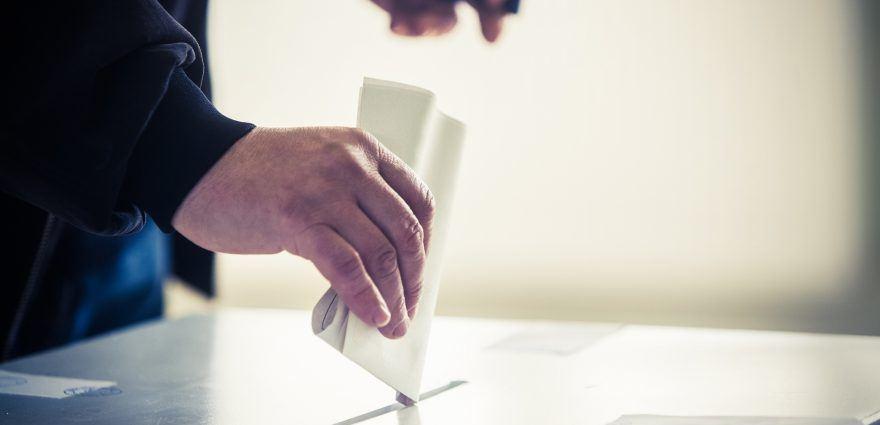 Foto: Ein Wähler steckt im Wahllokal seinen Stimmzettel in die Wahlurne
