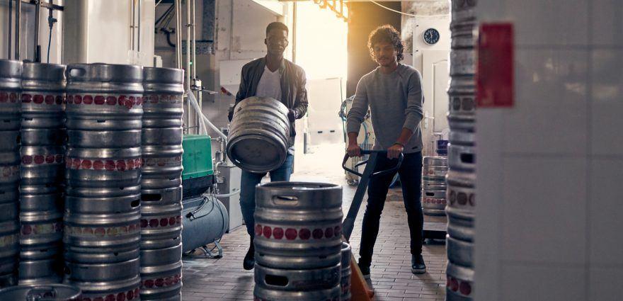 Foto: Zwei Kollegen transportieren Bierfässer in einer Brauerei