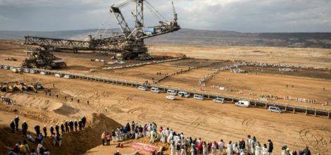 Foto: Aktivistinnen von Ende Gelände in Tagebaugrube mit Kohlebagger
