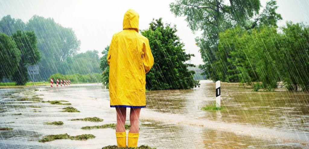 Foto: Mit Gummistiefeln auf überfluteter Straße