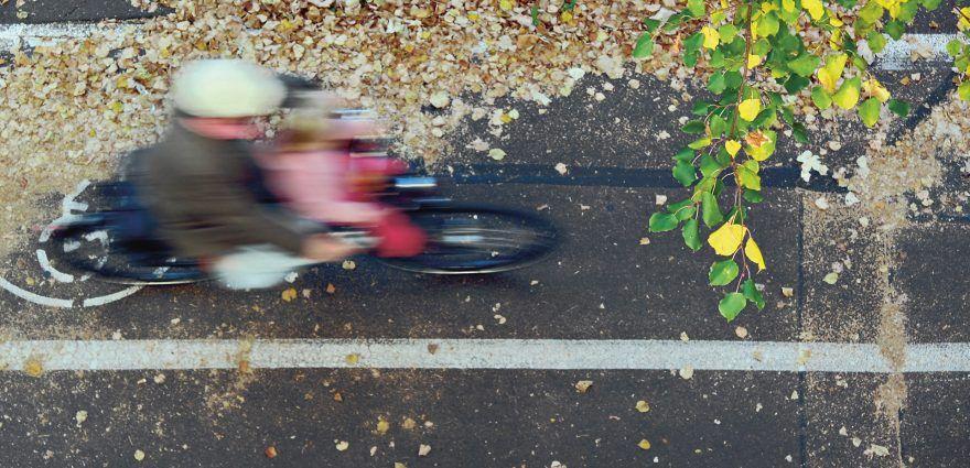 Foto: Radfahrer fährt mit Enkelkind im Herbst auf Radweg