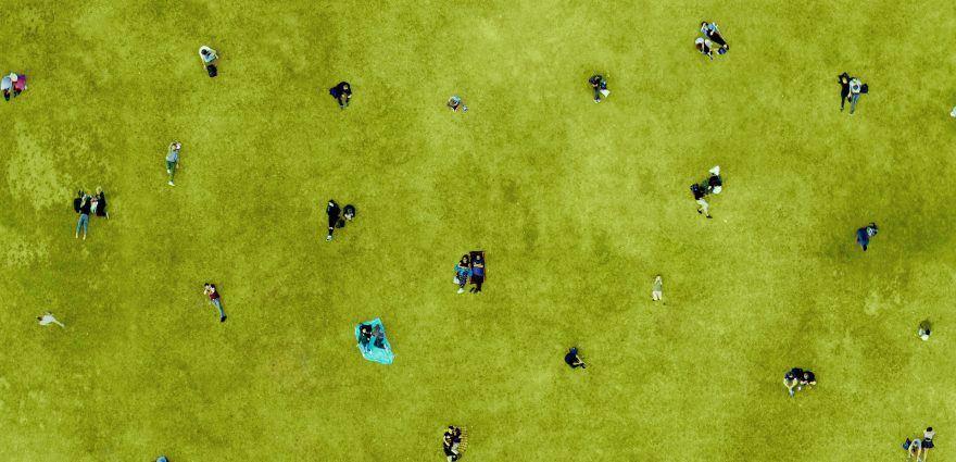 Foto: Viele Menschen mit Abstand auf einer Wiese