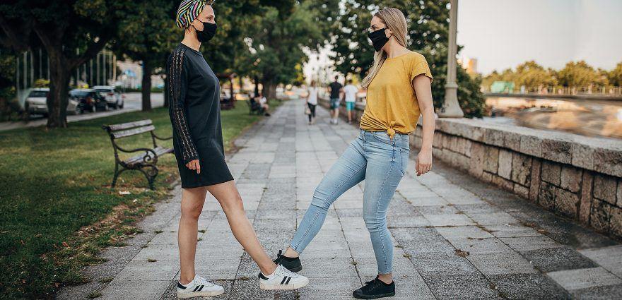 Foto: Zwei Frauen mit Maske begrüßen sich