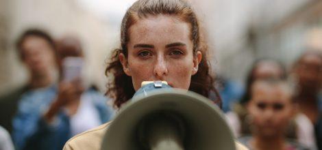 Foto: Junge Frau mit Megafon auf einer Demo